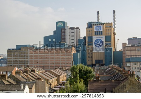 LONDON, UK - SEPTEMBER 10, 2014: View over houses in Silvertown towards the Tate and Lyle sugar refinery which produces both sugar crystals and Lyons Golden Syrup. - stock photo
