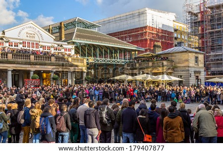 LONDON, UK - 1ST MARCH 2014: The Front of Covent Garden Market showing people gathering around watching an entertainer - stock photo