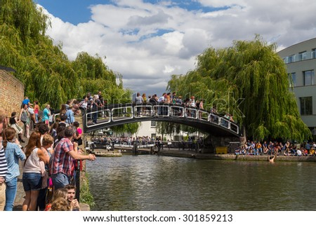 LONDON, UK - 19TH JULY 2015: A bridge in Camden Lock with lots of people on the bridge and at the side of the water. A man can be seen climbing out of the water. - stock photo