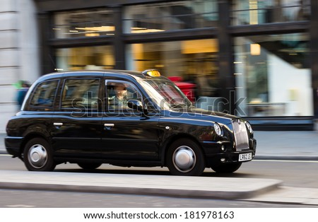 LONDON, UK - 16TH MARCH 2014: A Taxi moving down a street in London with a shop window in the background - stock photo