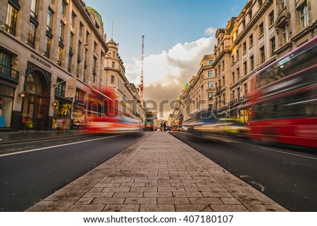 LONDON, UK - 24TH MARCH 2015: A view of Regent Street during the day, showing shops, buildings and the blur of people and traffic - stock photo