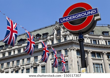 LONDON, UK - 24TH MAY 2012: London Underground sign and Union Flags in London. - stock photo