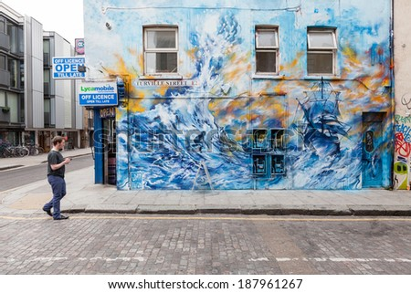 LONDON, UNITED KINGDOM - APRIL 18, 2014: Shoreditch, in the heart of the trendy East End of London, has become synonymous with the UK street art scene, attracting visitors from all over the world. - stock photo