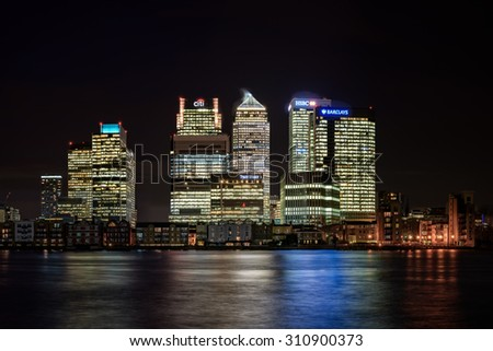 London, United Kingdom - January 26, 2015: Night panoramic view across river Thames to skyscrapers district Canary Wharf in London as seen on 26 of January, 2015. Has copy space in clear black sky. - stock photo