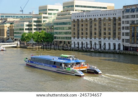 LONDON, UNITED KINGDOM - JULY 1, 2014: A City Cruises tour boat sails on the Thames River near London Bridge Hospital. Thames is the longest river in England with 346 km (215 miles) long. - stock photo