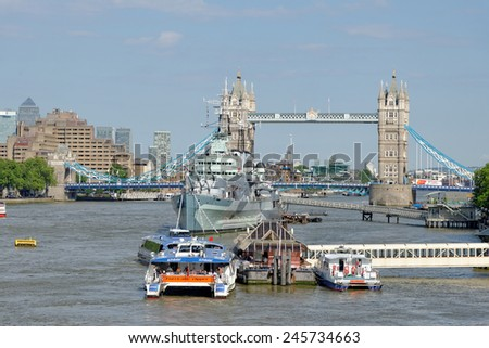 LONDON, UNITED KINGDOM - JULY 1, 2014: A City Cruises tour boat sails on the Thames River near Tower bridge. Thames is the longest river in England with 346 km (215 miles) long. - stock photo