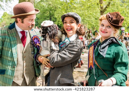 London, United Kingdom - May 14, 2016: Tweed Run (bicycle ride with a style) at picnic near Albert Memorial in Kensington Gardens, Hyde Park. Happy riders with a dog in a hat - stock photo