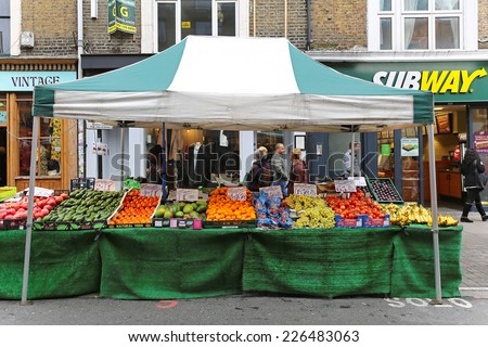 LONDON, UNITED KINGDOM - NOVEMBER 24: Brick Lane Market in East London on NOVEMBER 24, 2013. Temporary street market stall with fruits and vegetables on Sunday in London, United Kingdom. - stock photo