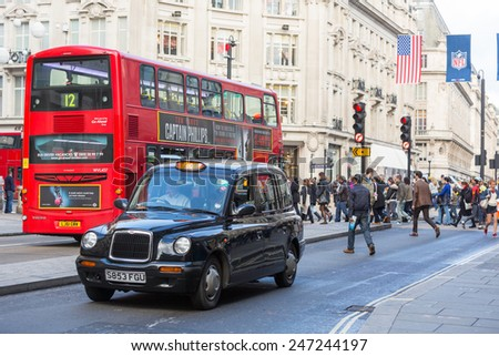 LONDON, UNITED KINGDOM - OCTOBER 25, 2013: Famous Black Cab and Double-Decker Red Bus next to Oxford Circus with people crossing the street on background. - stock photo