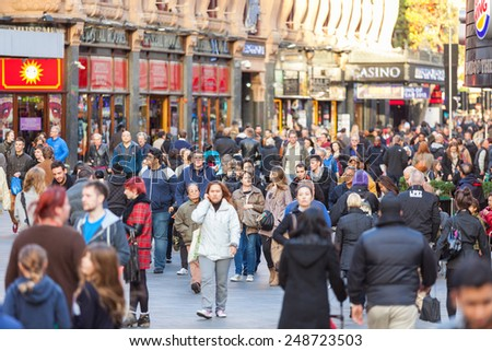 LONDON, UNITED KINGDOM - OCTOBER 30, 2013: Leicester Square crowded with tourists and commuters at sunset - stock photo