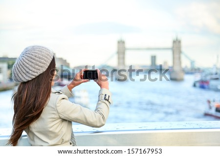 London woman tourist taking photo on Tower Bridge with mobile smart phone camera. Girl enjoying view over the River Thames, London, England, Great Britain. United Kingdom tourism concept. - stock photo