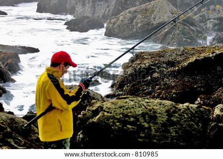 Lone Fisherman Rock Fishing - stock photo