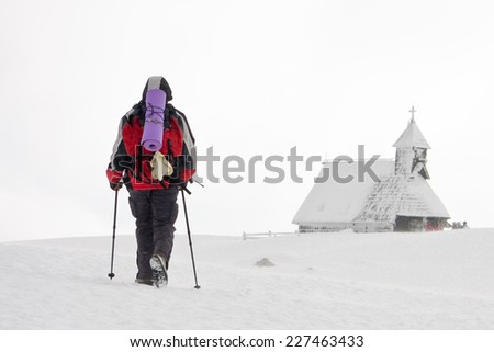Lone hiker going to the church of Snowy Mary on Velika planina in a wind blowing snow, Slovenia - stock photo