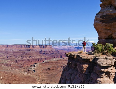 Lone hiker looks over Canyon Lands valley and Mesa in Utah - stock photo