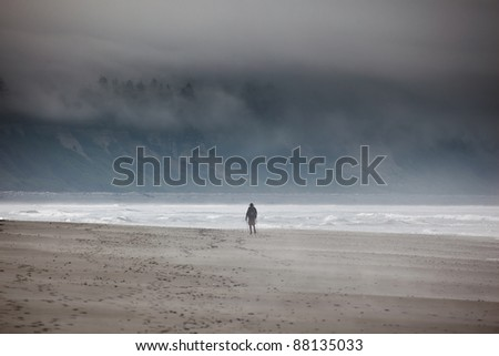Lone hiker on the foggy beach - stock photo