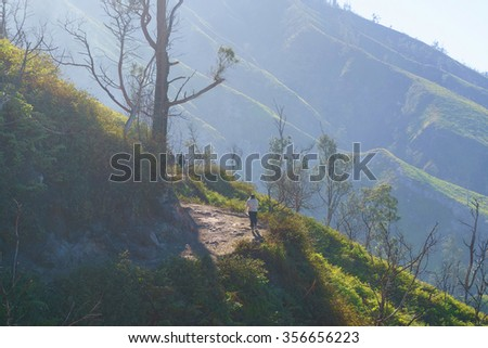 lone lady hiker on misty trail over looking beautiful and romantic tropical mountain.  - stock photo