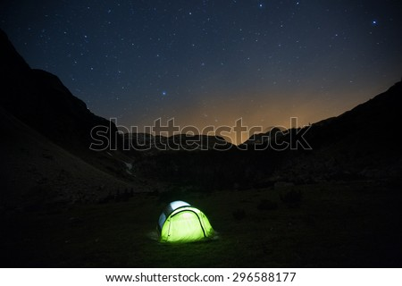 Lone, lit pop-up tent standing on a mountain pasture under the starry sky, night landscape with bright sun flare in the background. Outdoor lifestyle and sleeping under stars concept and background.  - stock photo