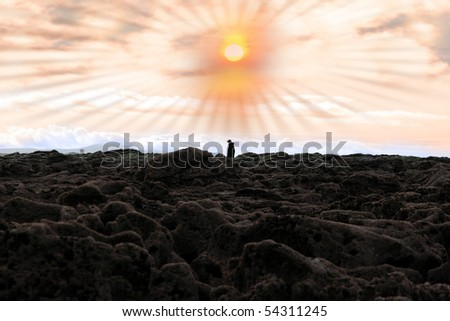 lone man walking among rocks with sun beaming down on the ballybunion coastline on irelands west coast - stock photo
