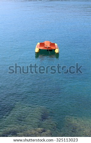 Lone Pedalo in a blue sea. Vacation image. - stock photo