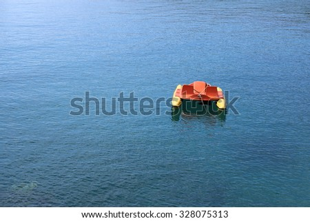 Lone Pedalo, recreational boat, surrounded by calm open water with copy space. - stock photo