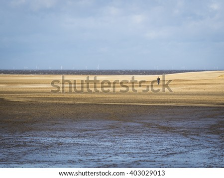 Lone person on a sandy beach - stock photo