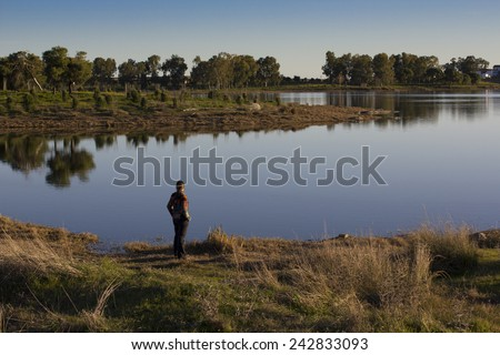 Lone person standing facing away from the camera looking out over a tranquil lake with reflections in early morning light - stock photo