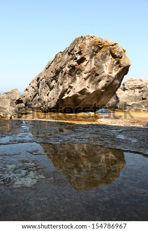 Lone rock on a lake shore with reflection in the water - stock photo