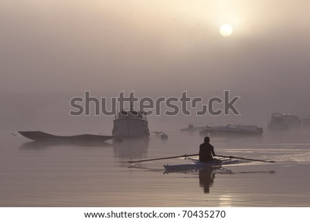 Lone rower passing silhouetted boats on the river Thames - stock photo