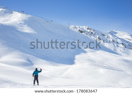 Lone skier waving on a snowy mountain peak covered in pristine fresh white powder as he or she prepares to descend the ski run in a beautiful cold sunny winter landscape - stock photo