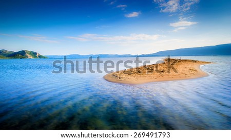Lone small sandy island in the middle of blue sea - stock photo