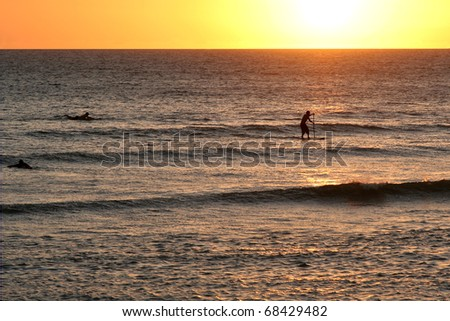Lone standup paddleboard surfer on the ocean at sunset. - stock photo