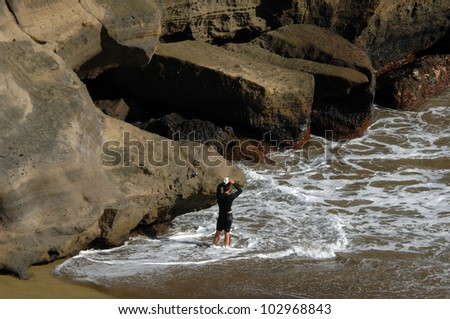 Lone tourist gets ready to fish the famous Green Sand Beach at South Point on the Big Island of Hawaii. - stock photo