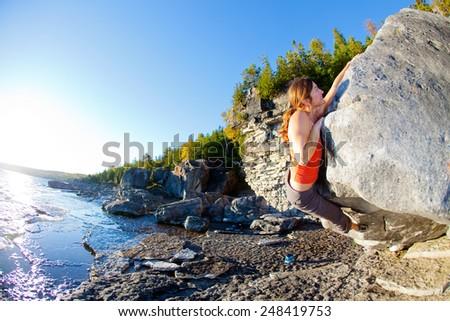 Lone woman rock climbing on the beach - stock photo