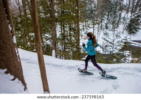 Lone woman  running in the forest on snowshoes - stock photo