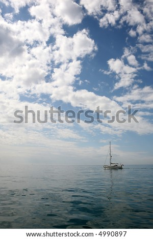 Lone yacht on the open ocean - stock photo