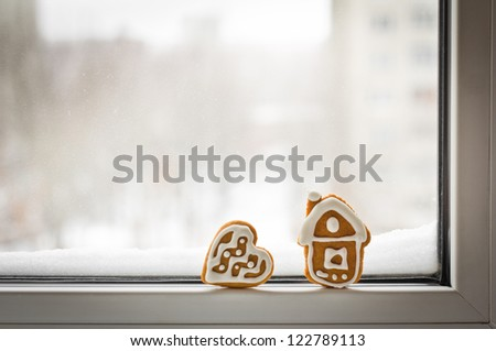 Loneliness. Christmas gingerbread cookies on the winter window with snow with copy space for your text - stock photo