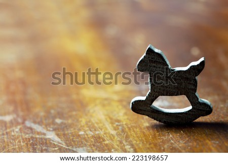 Loneliness concept: wooden rocking horse on wooden background - stock photo