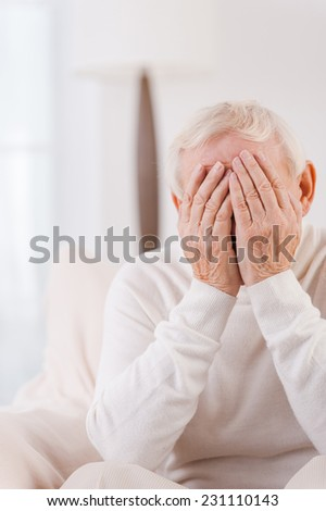 Loneliness. Frustrated senior man covering his face by hands while sitting in chair  - stock photo