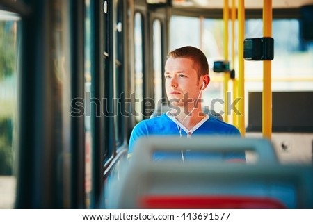 Loneliness man is wearing headphones and listening to music. Everyday life and commuting to work by public transportation. Handsome young man is traveling by tram.  - stock photo