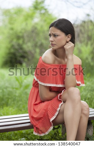 lonely beautiful girl sitting on a park bench waiting for someone and think - stock photo