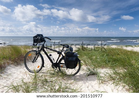 Lonely bike standing on dune on sea coast - stock photo