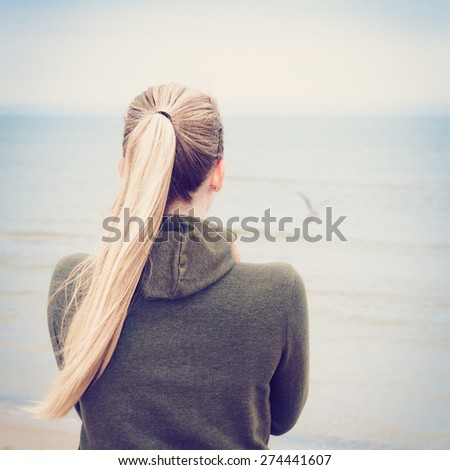 lonely blond girl looking at the sea. Selective focus. - stock photo