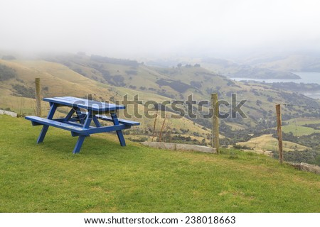 Lonely Blue Picnic table in lush green park on scenic viewpoint of Akaroa, New Zealand. - stock photo