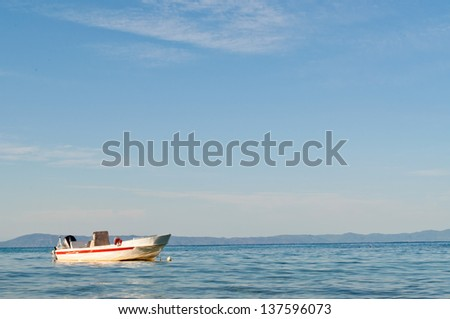 Lonely boat on the sea and sky in the background - stock photo