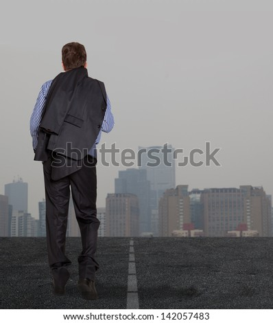Lonely businessman walking on a road - stock photo