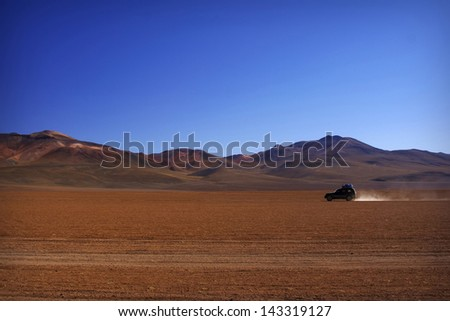 Lonely car going trough Salvador Dali Desert in Altiplano, Bolivia  - stock photo