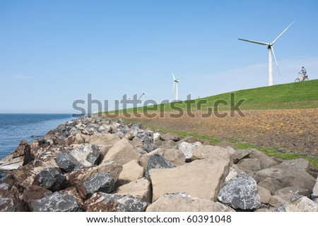 Lonely cyclist riding at an endless dike with windmills in the Netherlands - stock photo