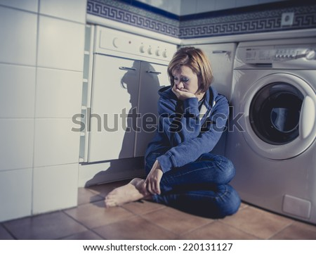 lonely depressed and sick woman sitting alone on kitchen floor in stress , depression and sadness feeling miserable in barefoot looking desperate - stock photo