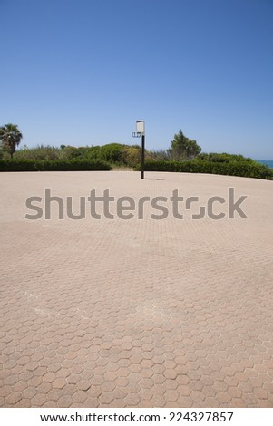 lonely far basketball court on pavement street - stock photo