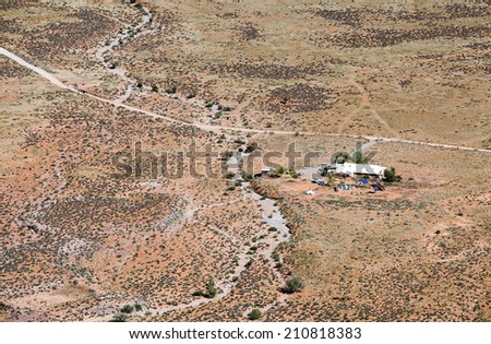 Lonely farm house in desert surrounded by solar panels - stock photo